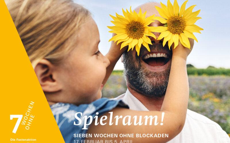Spielraum. 7 Wochen ohne Blockaden. Ein Kind hält einem Mann zwei Sonnenblumen vor die Augen.